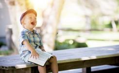 Foto van jongetje dat aan het lachen is met een boek