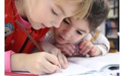 foto van twee kinderen die aan het schrijven zijn