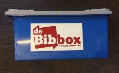 Een foto van een bibbox, een blauwe bak vol boeken
