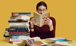 Lezende vrouw bij stapel boeken