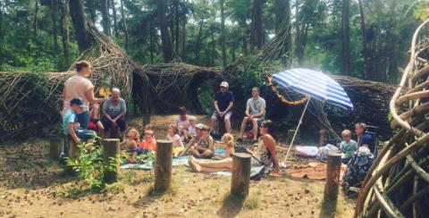 Foto van kinderen die in het bos luisteren naar een verhaal