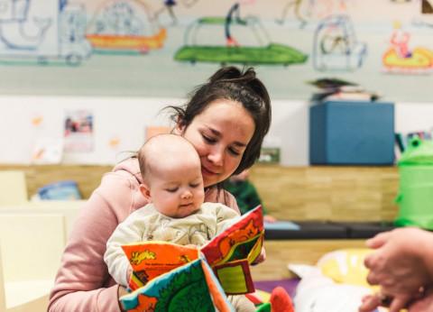 Vrouw leest voor aan baby